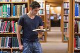 Man standing at the library holding a book
