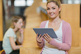 Woman standing in library with tablet pc