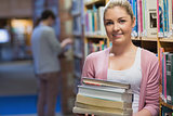 Woman holding pile of books in college library
