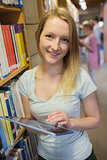 Woman holding tablet pc standing in library