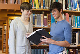 Students standing in library looking at book