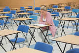 Student studying at desk in empty exam hall