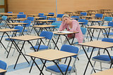 Student studying in empty exam hall