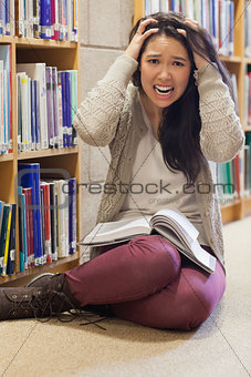 Stressed student sitting on library floor