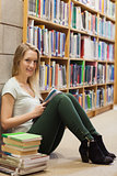 Girl sitting on the library floor holding a book
