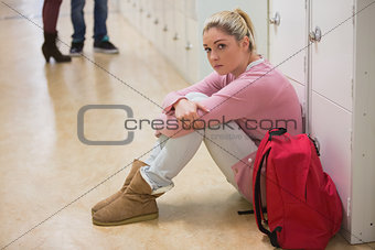 Student sitting against lockers