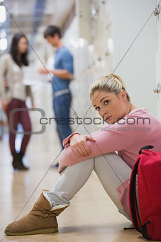 Sad student sitting against lockers