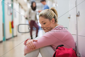 Student sitting on the floor at the hallway looking disappointed