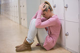 Upset student sitting on floor of hallway