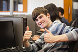 Man sitting at computer giving thumbs up