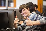 Man sitting at computer giving thumbs up
