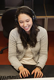 Female student sitting at the computer with headphones