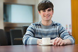 Student sitting at table drinking coffee in college cafe