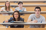 Students sitting at the desk while smiling