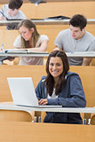 Smiling student in lecture with laptop