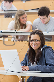 Girl sitting at the lecture hall with laptop