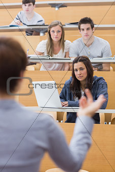 Students sitting at the lecture hall listening