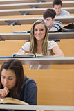 Student sitting at the lecture hall while smiling