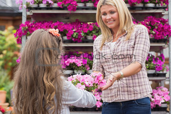 Little girl giving flower pot to her mother