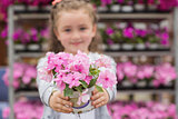 Little girl with flowers in garden center