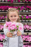Little girl smiling and holding a flower pot