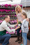 Employee giving a flower to little girl in garden center