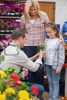 Little girl getting a present from garden center worker