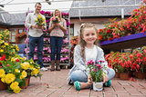 Family holding flower pots in garden center