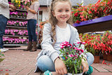 Little girl holding flowers sitting on path