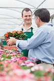 Employee giving a box of flowers to man