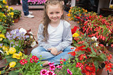 Little girl sitting on path surrounded by flowers