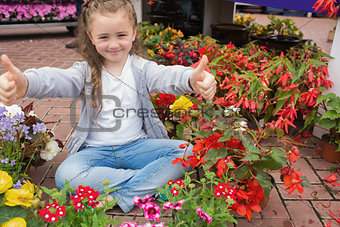 Little girl giving thumbs up while sitting on the floor