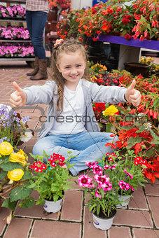 Little girl doing thumbs up sitting in garden centre