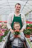Gardener and little child holding a flower