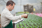 Man standing in greenhouse and taking notes
