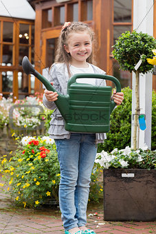 Little girl holding watering can while smiling
