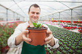 Cheerful man holding a potted plant