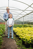 Gardener with granddaughter in greenhouse