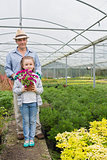 Little girl holding flower pot standing with her granddad