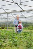 Man standing with granddaughter holding purple flowers