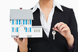 Businesswoman in suit holding a model house and key