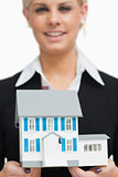 Smiling businesswoman holding a model house