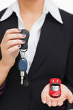 Woman holding key and small car in her palm