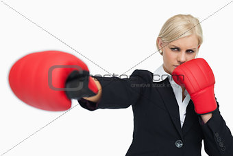 Blonde businesswoman with red gloves fighting
