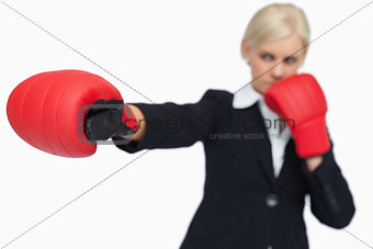 Blonde businesswoman with red gloves boxing