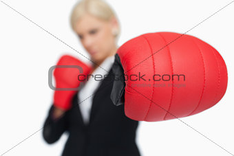 Blonde businesswoman with red boxing gloves fighting