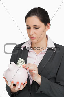 Image Description: Brunette putting dollars into a piggy-bank against