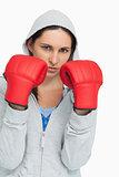 Brunette in sweatshirt wearing boxing gloves