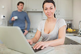 Young woman using laptop with man drinking coffee