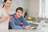 Young couple using laptop drinking red wine